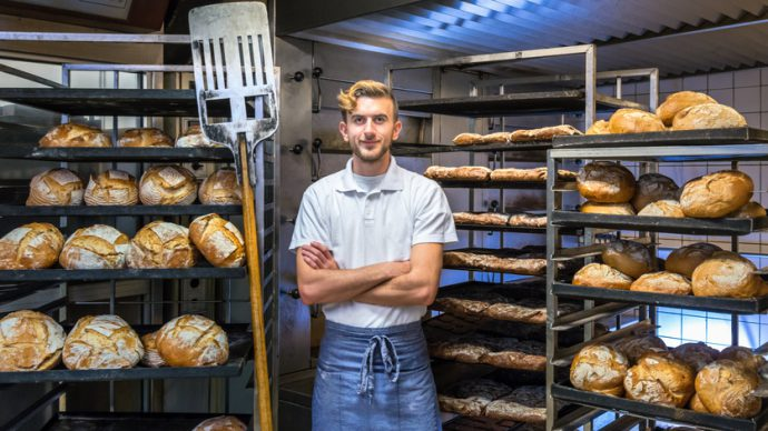 baker posing in his bakery bakehouse in the early morning between fresh baked artisan bread